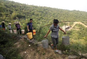 Farmers carry buckets to collect water on the outskirts of Loudi